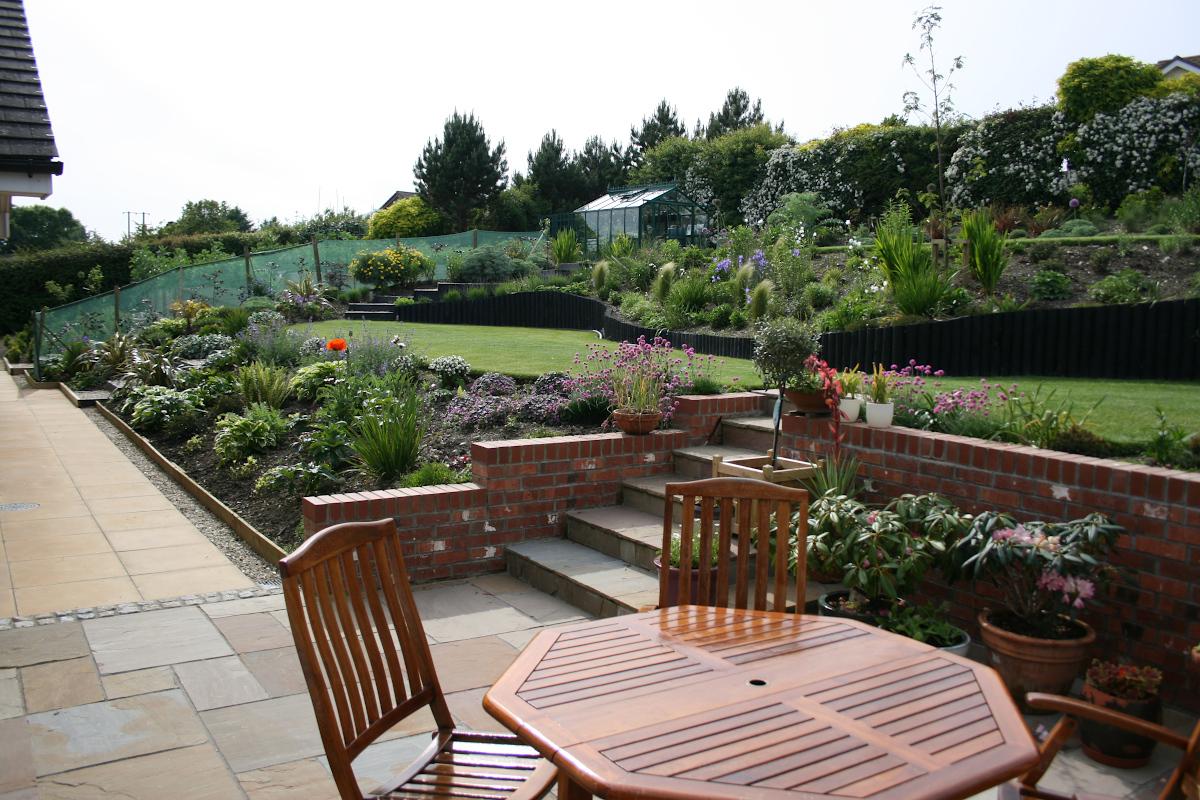 Garden dining set on deck within landscaped garden