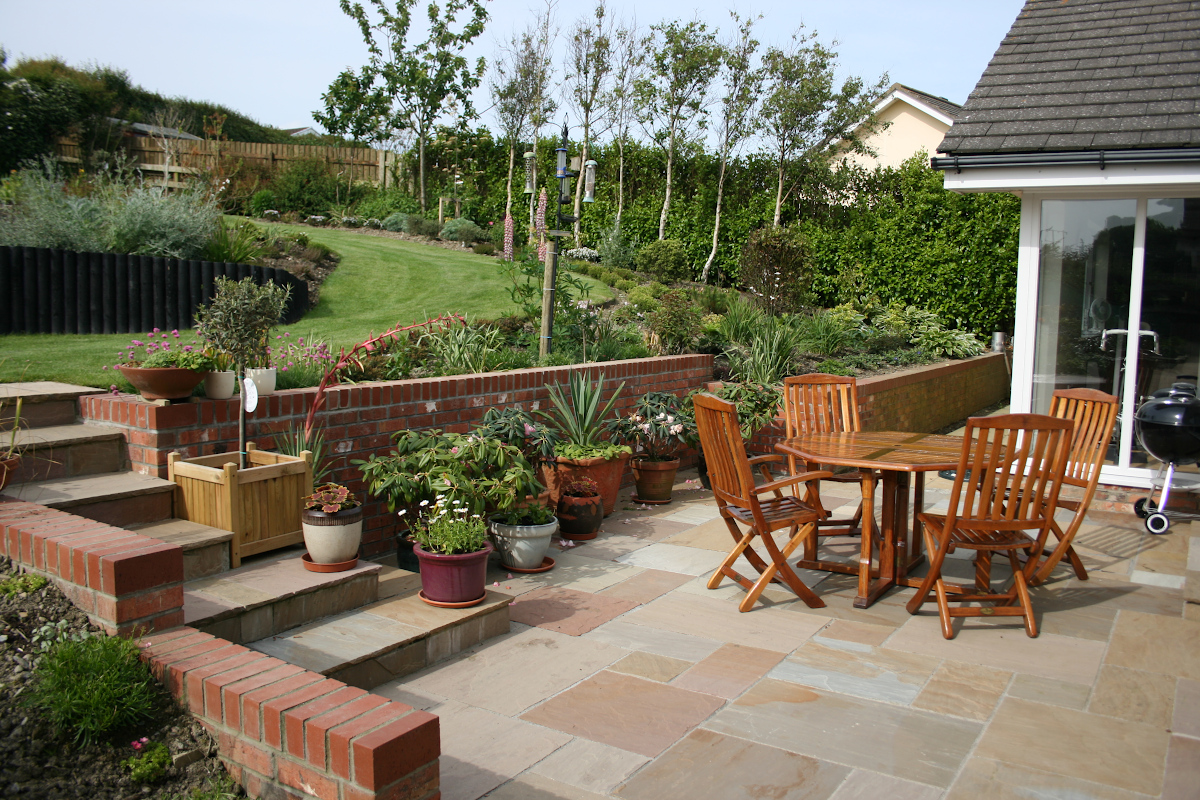 Garden design with patio, pots and table with chairs