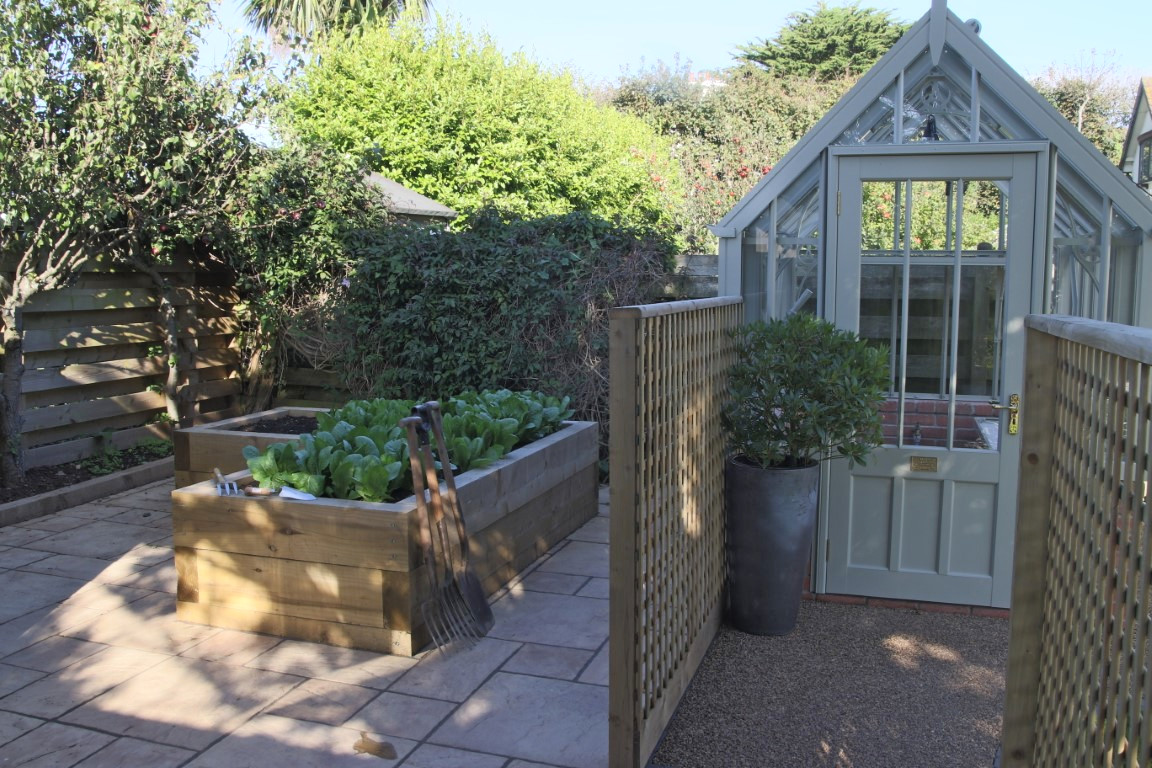 Kitchen garden with vegetables in raised bed and greenhouse