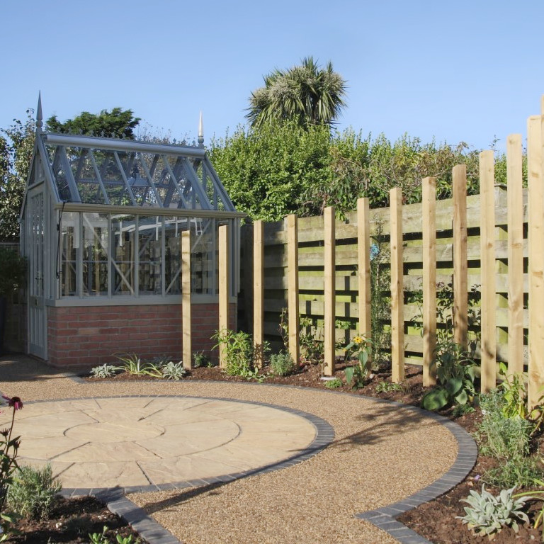 Circle of paving with vertical timber feature screen and greenhouse
