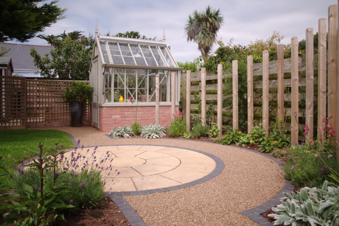 Circular paving with pathway and curved timber feature surrounded by planting