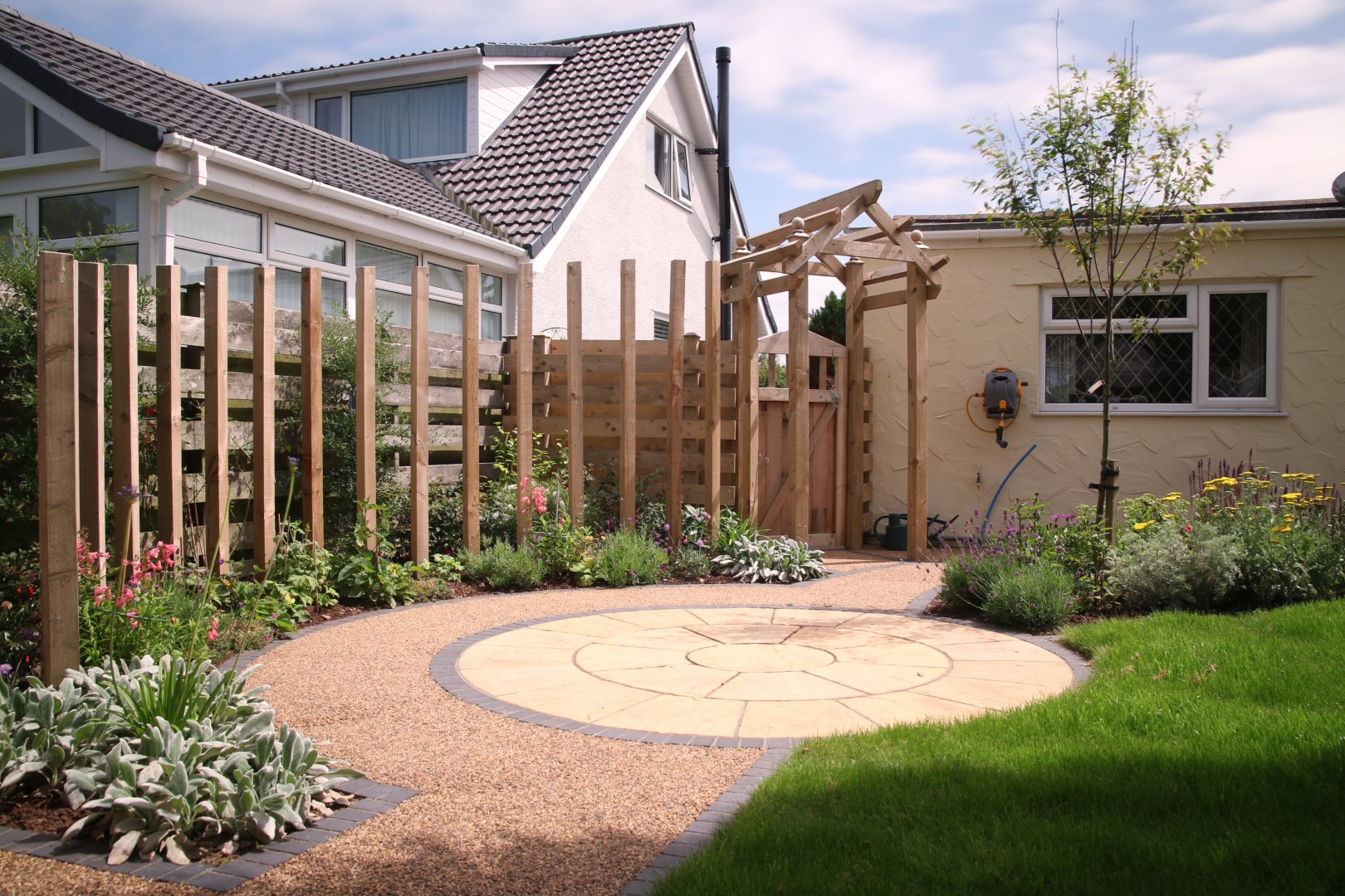 Circular paving and curved timber feature surrounded by flowers and plants