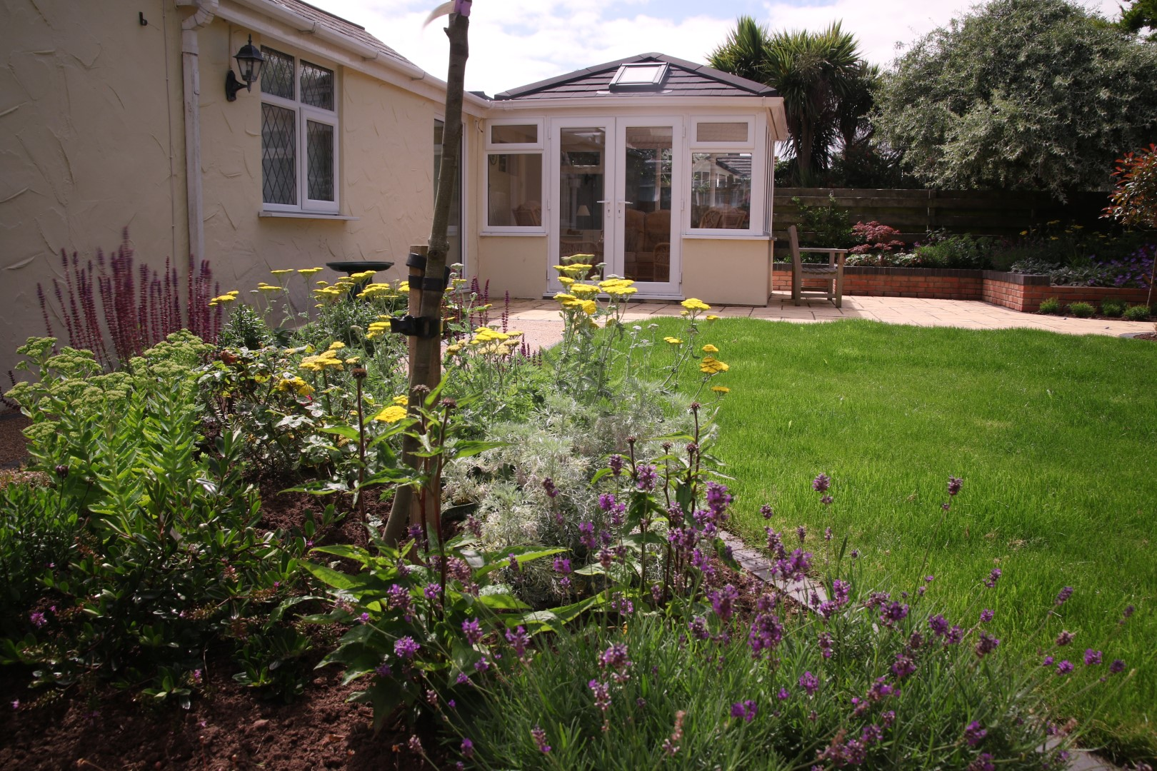 Purple and yellow flowers in decorative flower bed overlooked by a conservatory